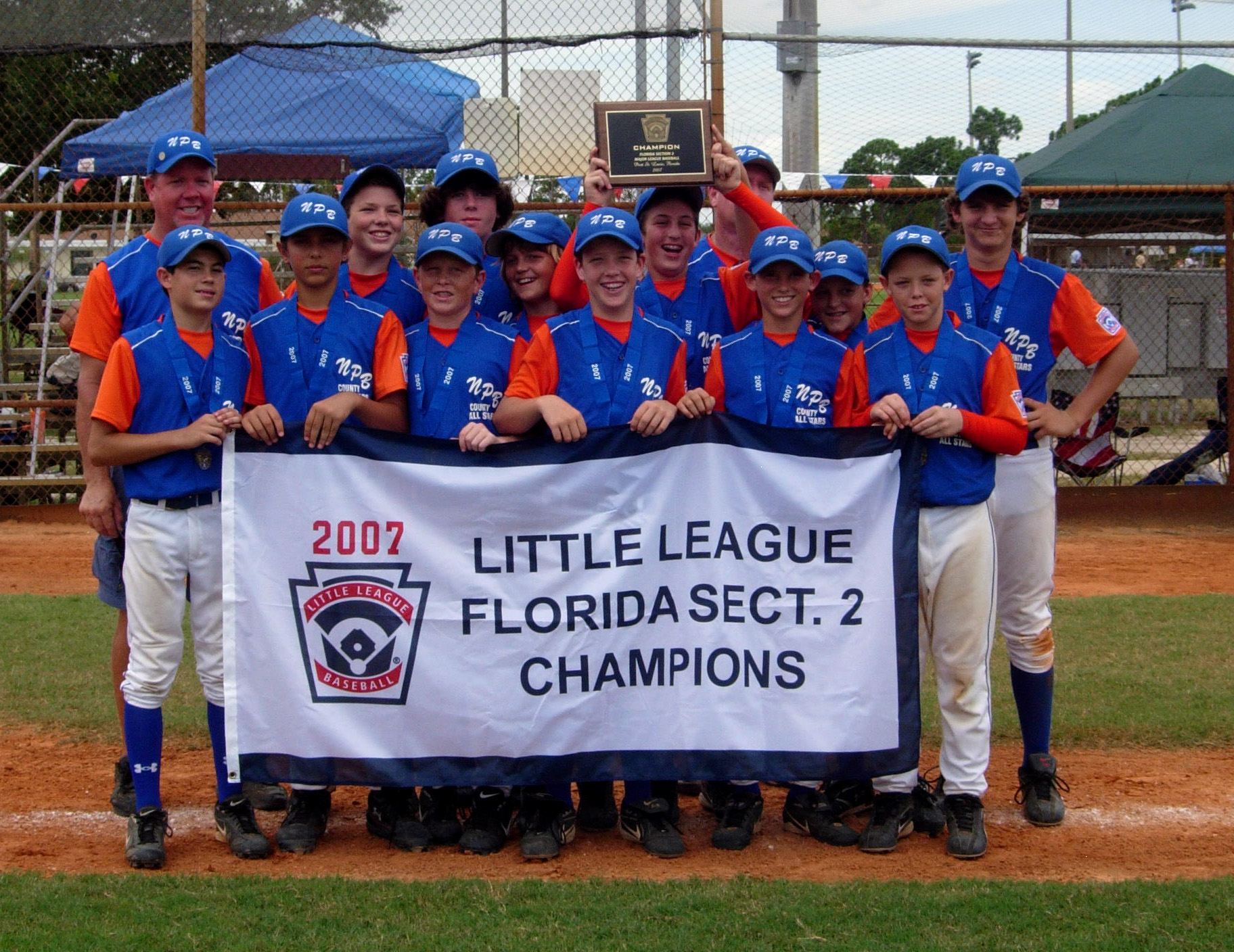 2007 North Palm Beach Little League Championship team in red and blue uniforms holding banner