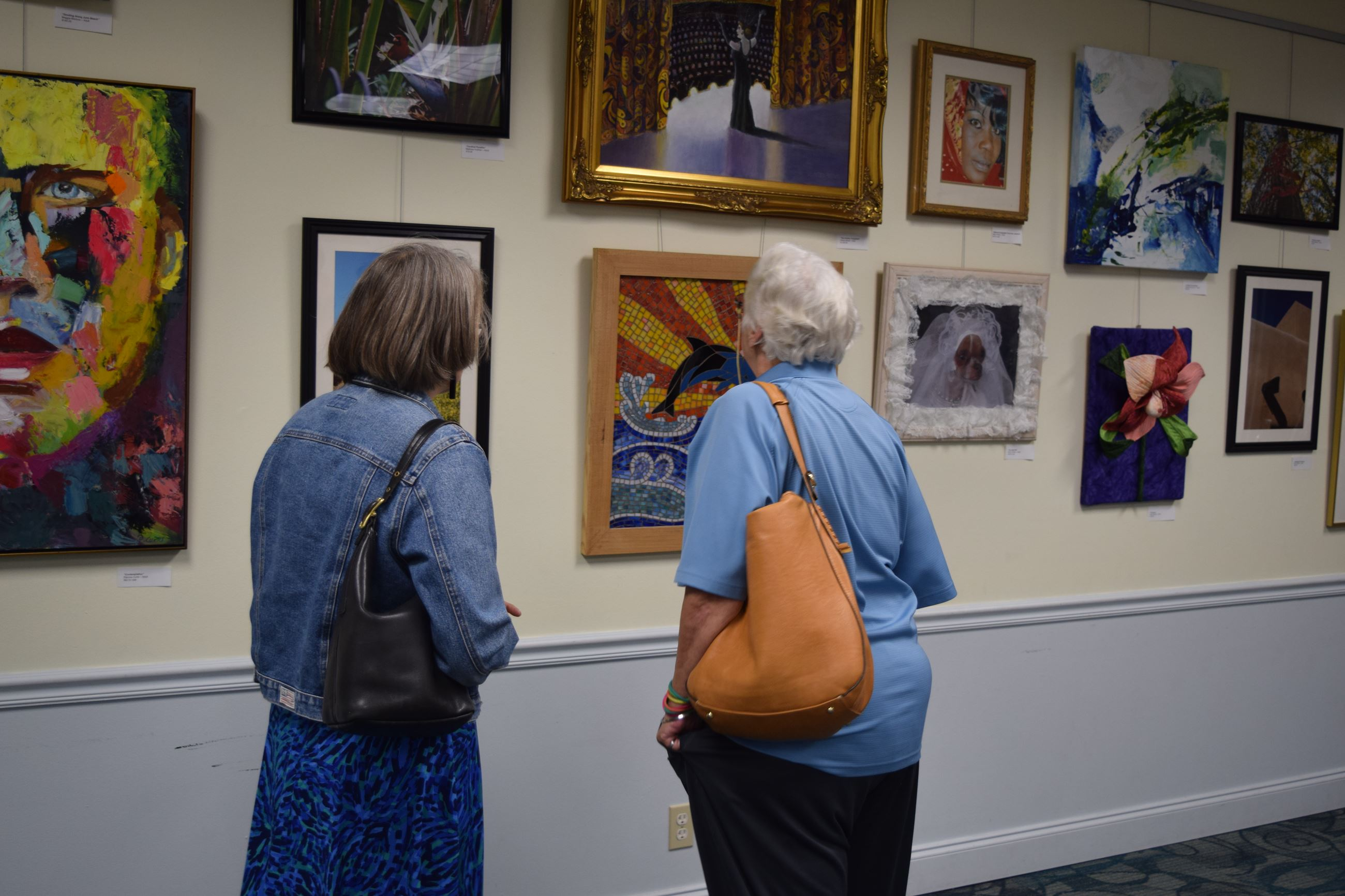 Two women looking at artwork on wall of gallery at Art Show