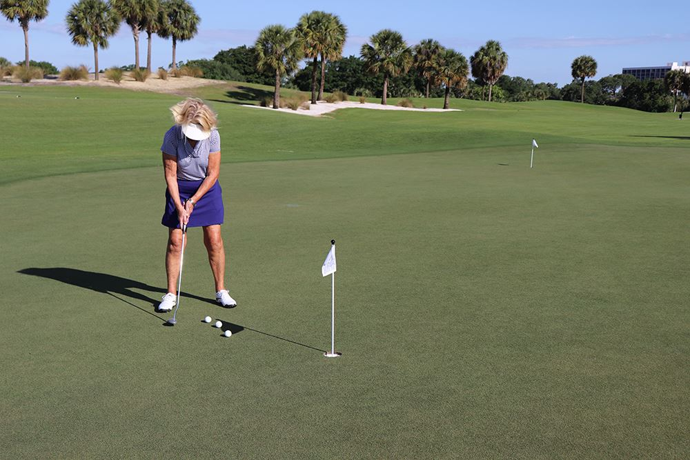 Woman practicing golf on putting green