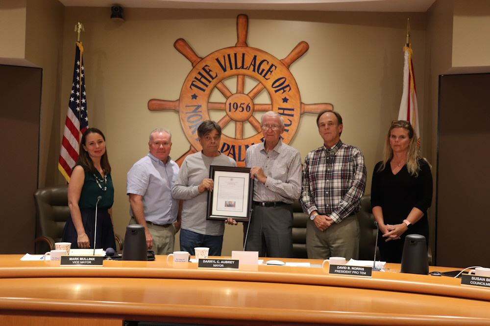 Village Council standing with David Teal, who is holding the commendation for Melissa Teal.