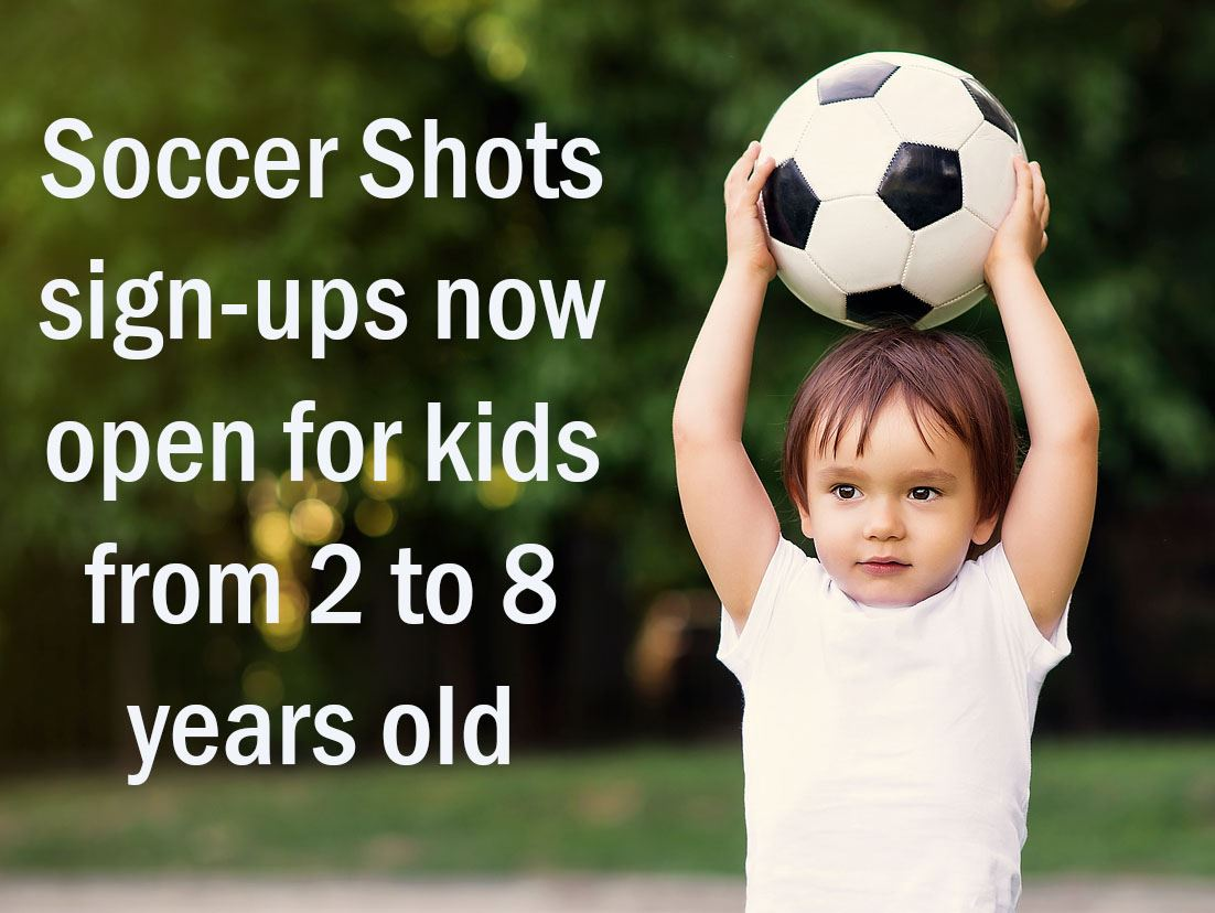 Boy toddler holding soccer ball over his head, with text saying &#34Soccer Shots sign-ups now open f