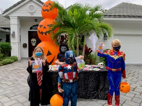Kids in costumes at Halloween table in front of house. Waiving.