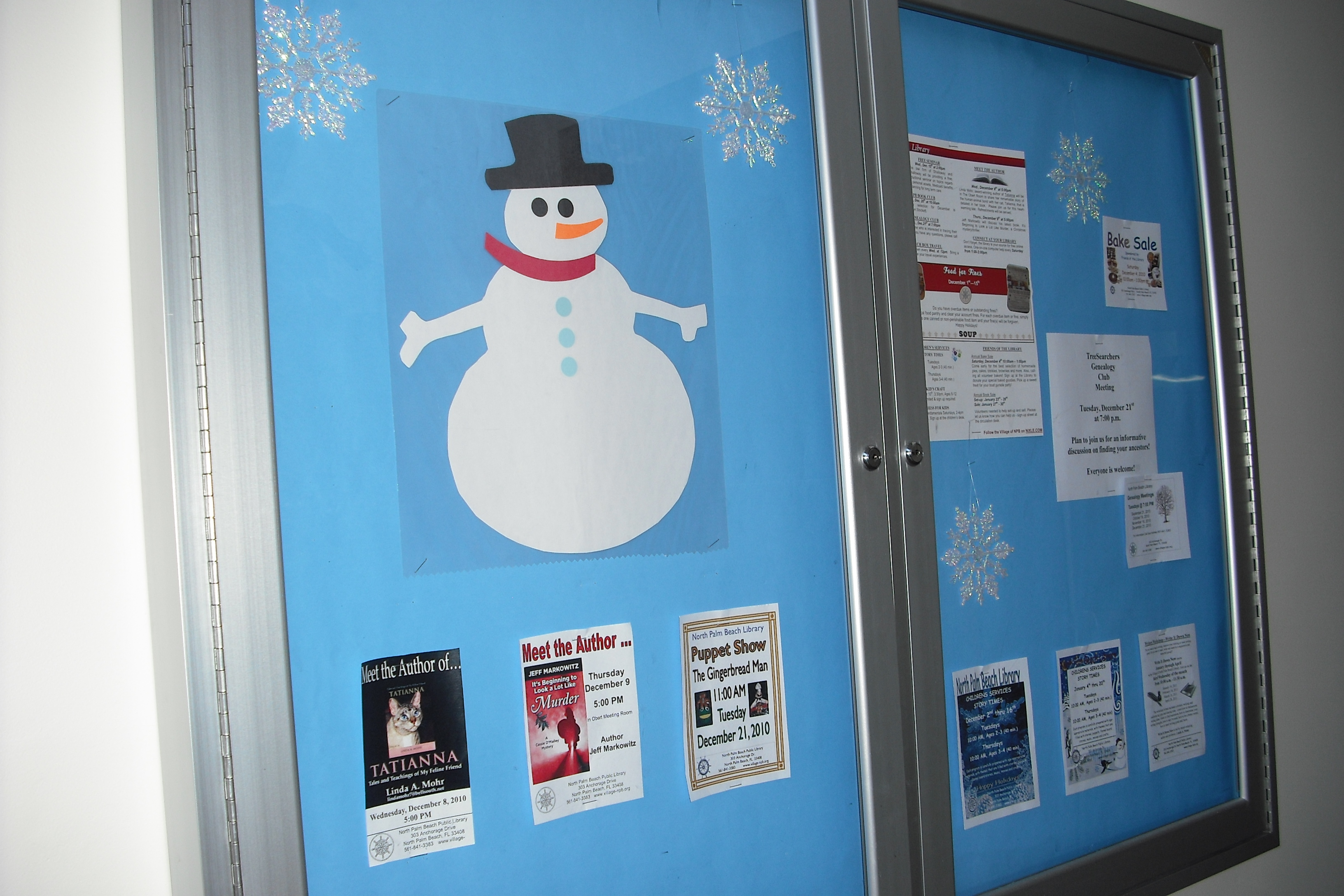A paper snowman sits above flyers for more events at the library