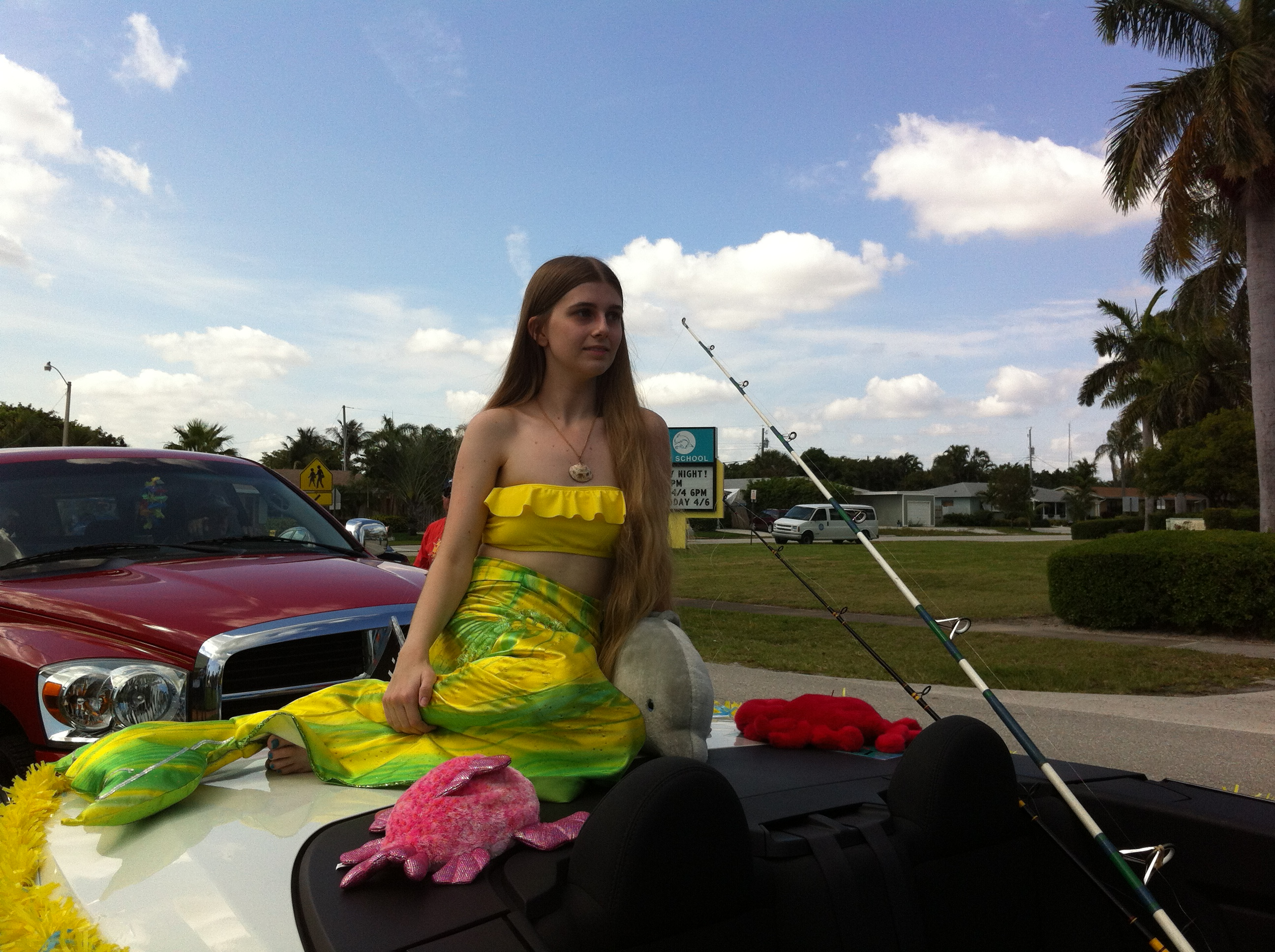 The mermaid sits on the back of the car during the parade