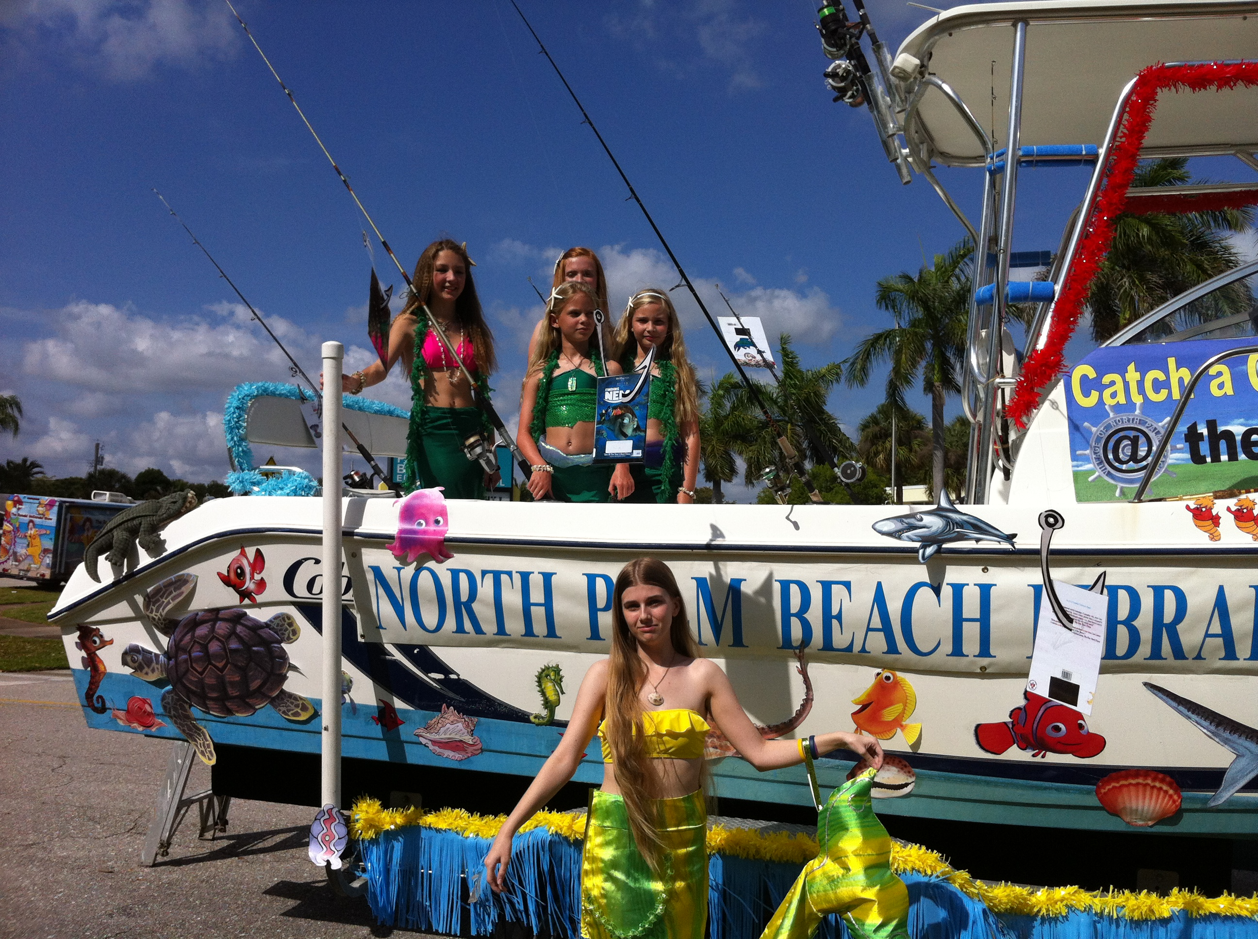 The mermaid stands in front of the float, with the other sea-ladies on the float