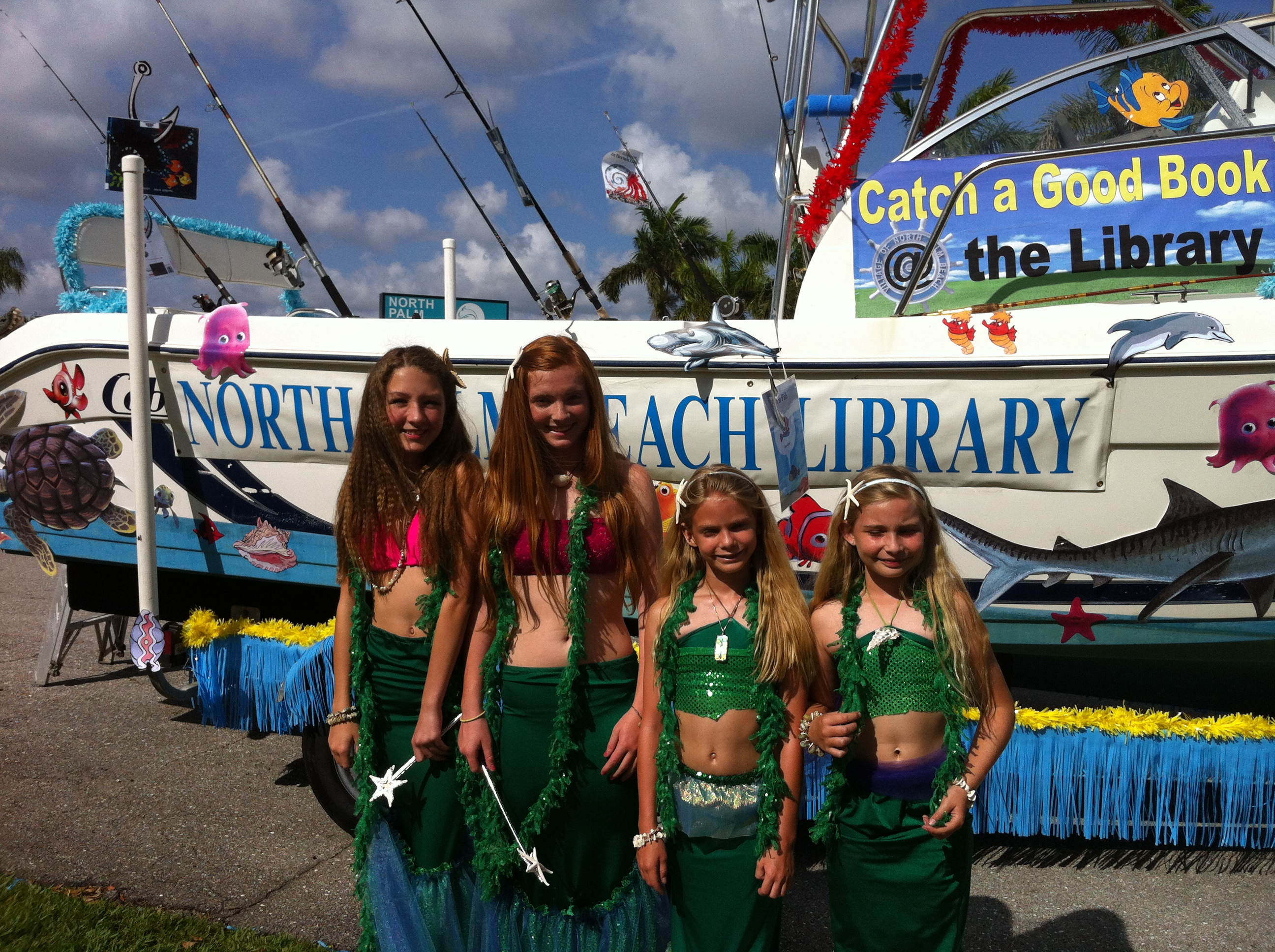 Some sea-ladies stand in front of the float