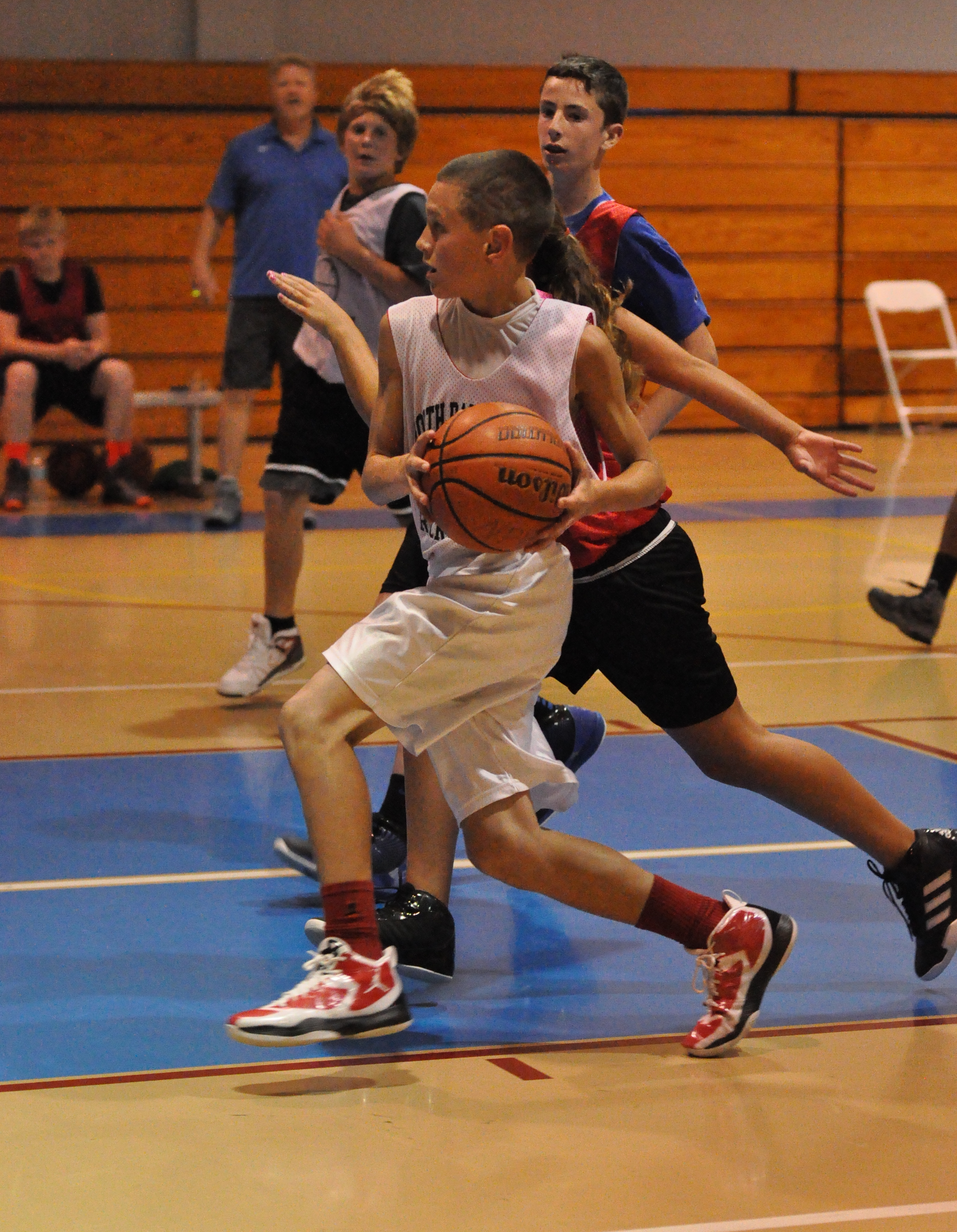 Boy playing basketball, driving to hoop past defender