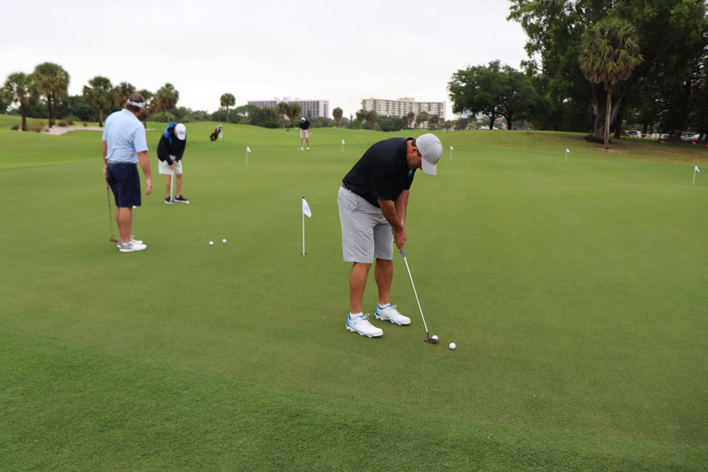 Golfer getting ready for putt shot on golf course opening day