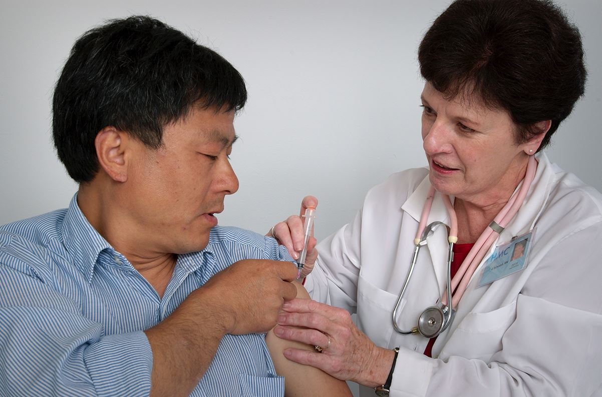 Health care worker giving shot to patient